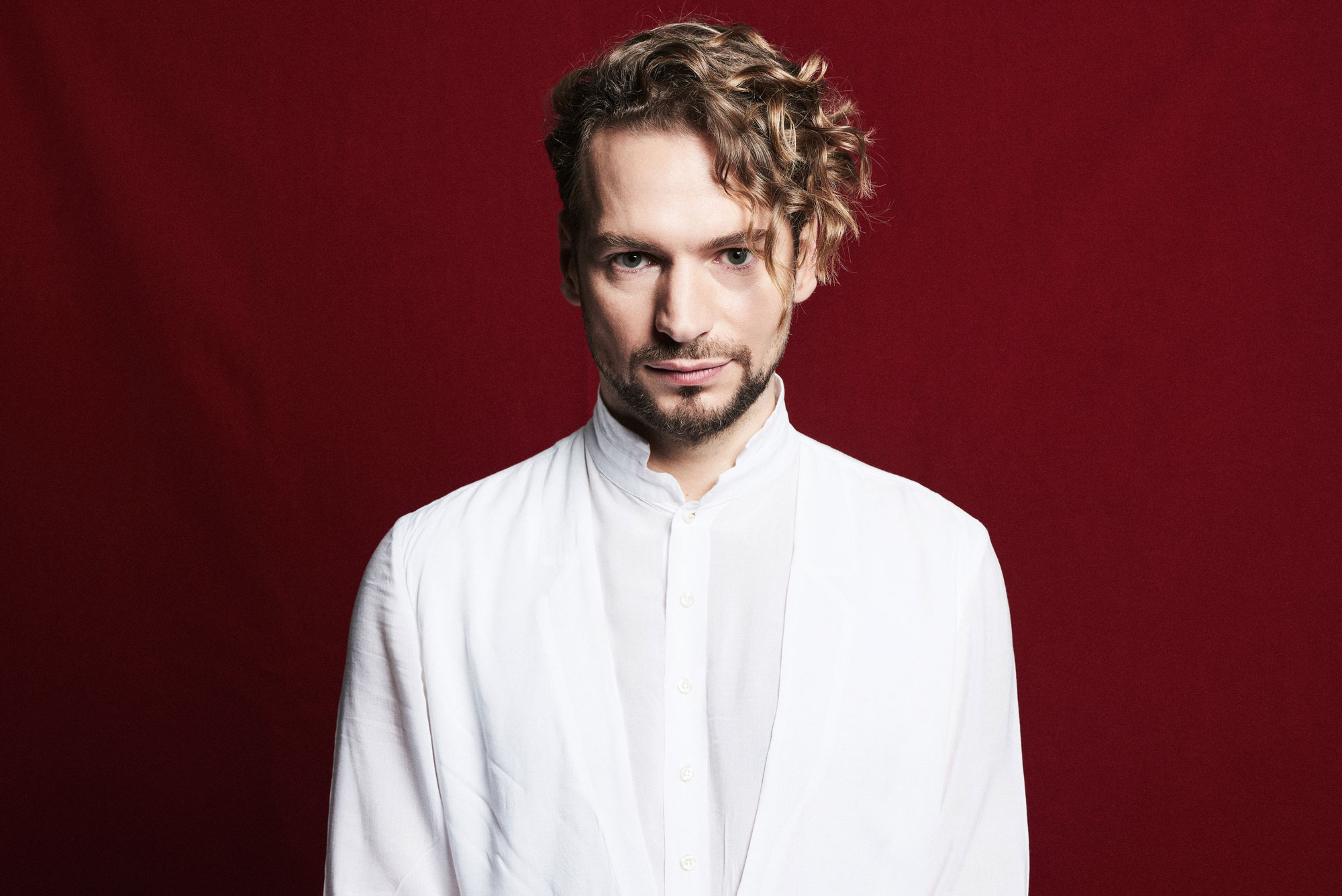Portrait photo of singer Felix Räuber in white clothes against a red background