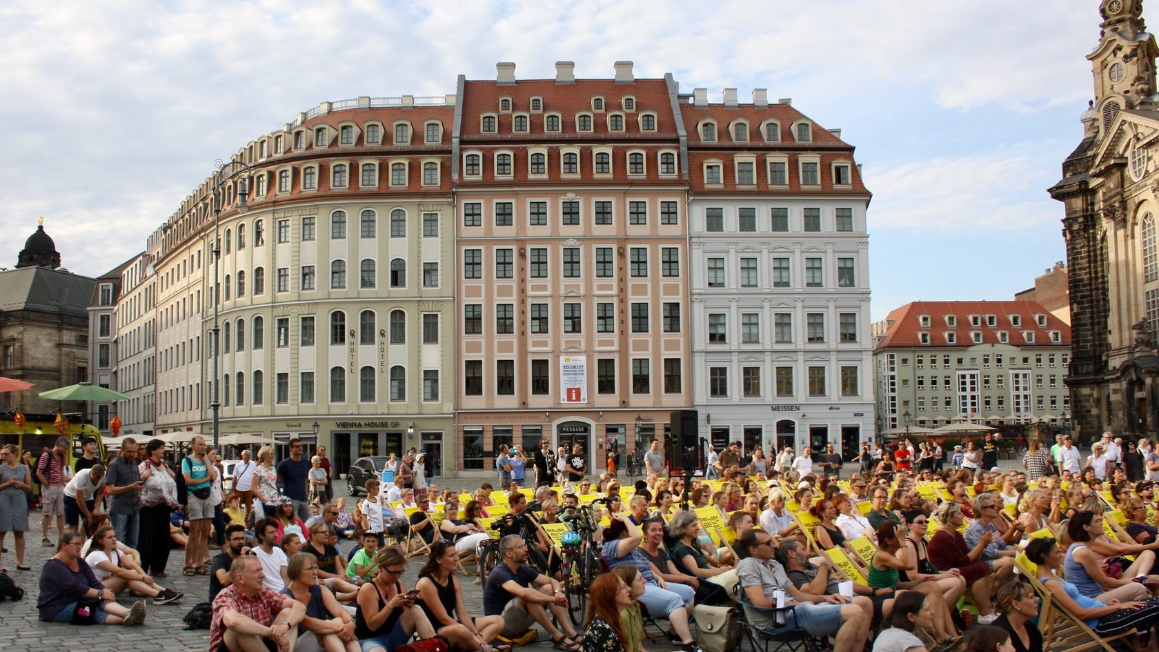Numerous people are sitting in deck chairs on Dresden's Neumarkt square. In the background houses and a part of the Dresden Frauenkirche can be seen.