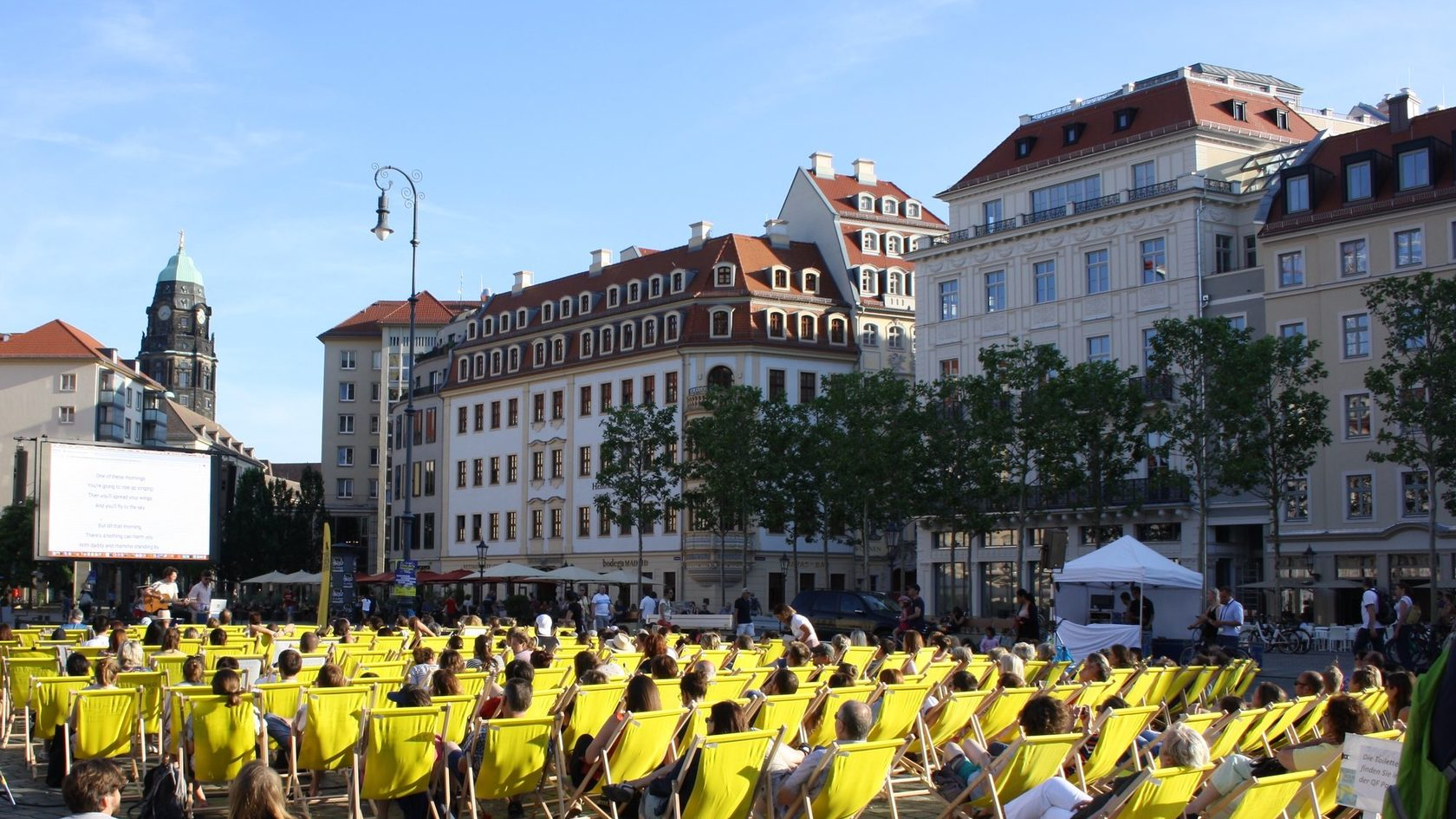 Numerous people are sitting in deck chairs on Dresden's Neumarkt square watching a movie on a mobile cinema screen.